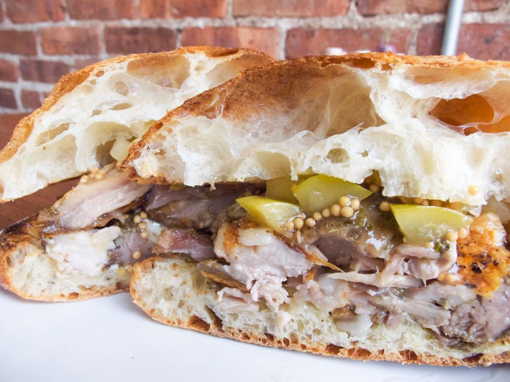 Man food the porchetta sandwich at pennypackers in