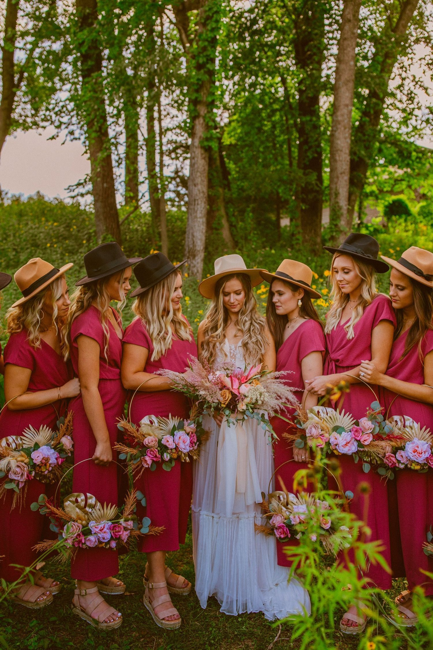 Literally the prettiest bride and her bridesmaids in Cedar Rapids, Iowa with pink bridesmaids JUMPSUITS and the most original wooden pink baskets holding their bouquets for their bouquets rings! Seriously to die for and the best pop of color for the most green forrest wedding! Also, I'm obsessed with the the cutest hats that they all wore!!! Best styled bridal party everrrrr! | Photo but: Olivia Markle Photography #bridesmaides #cedarrapidswedding #elopement #wedding #bridalpartystyle #pink #bri #bridesmaidjumpsuits