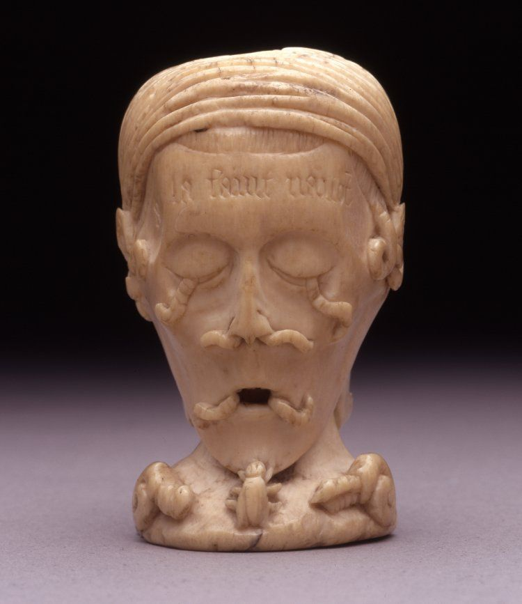 Memento mori; ivory; carved; one side depicts face being eaten by worms, other side depicts skull with toad in mouth; inscription on both sides in black paint; vertical pierced hole.  France, 16th century