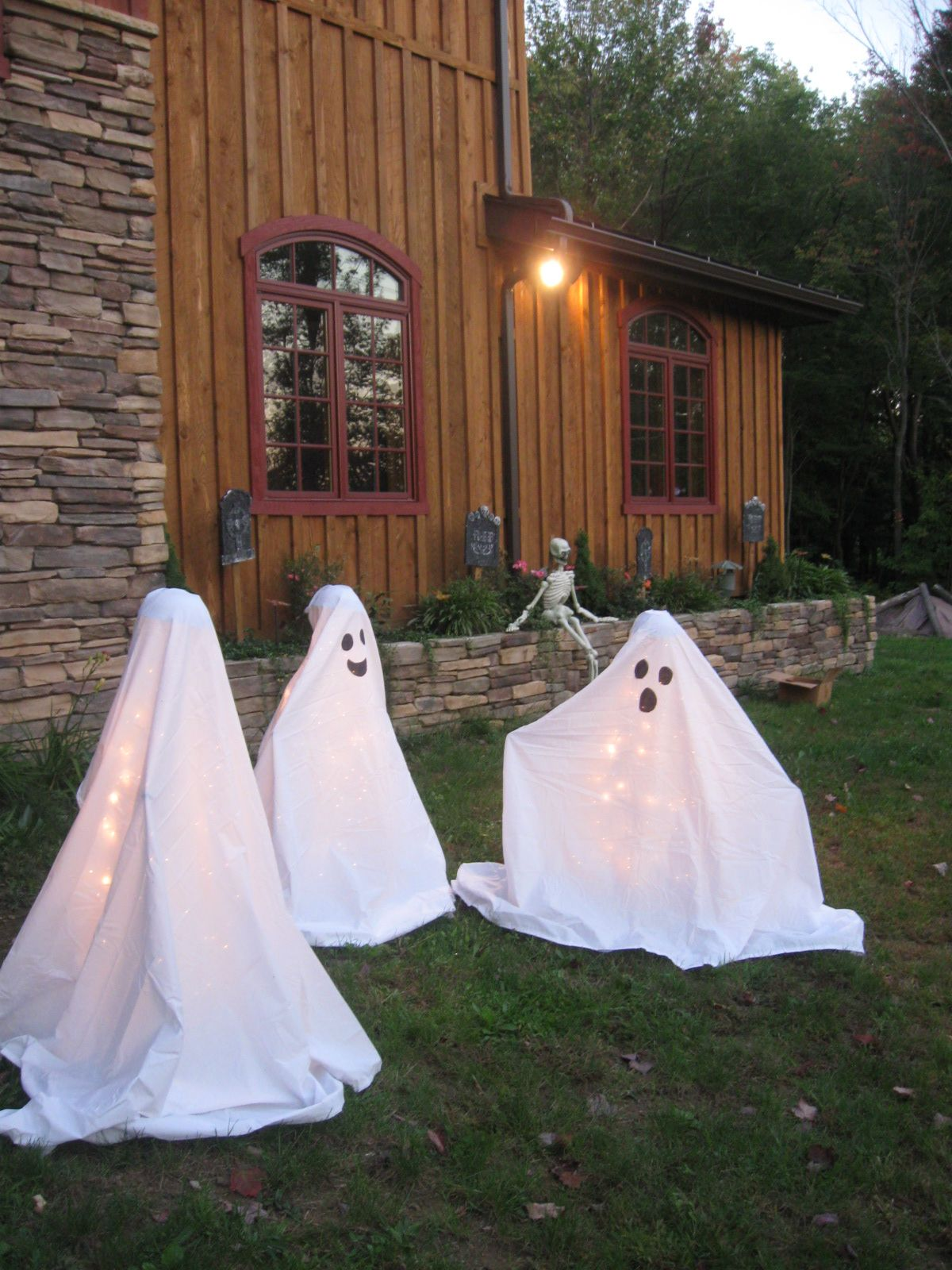 Easy DIY ghosts that I made...use tomatoe cage, place outdoor lights on it 50count or more, place something on the top of the cage (I glued styrofoam balls into cheap bowls), buy some cheap twin size white sheets, wrap it and there you have it friendly ghosties. I held sheets inplace with floral wire.