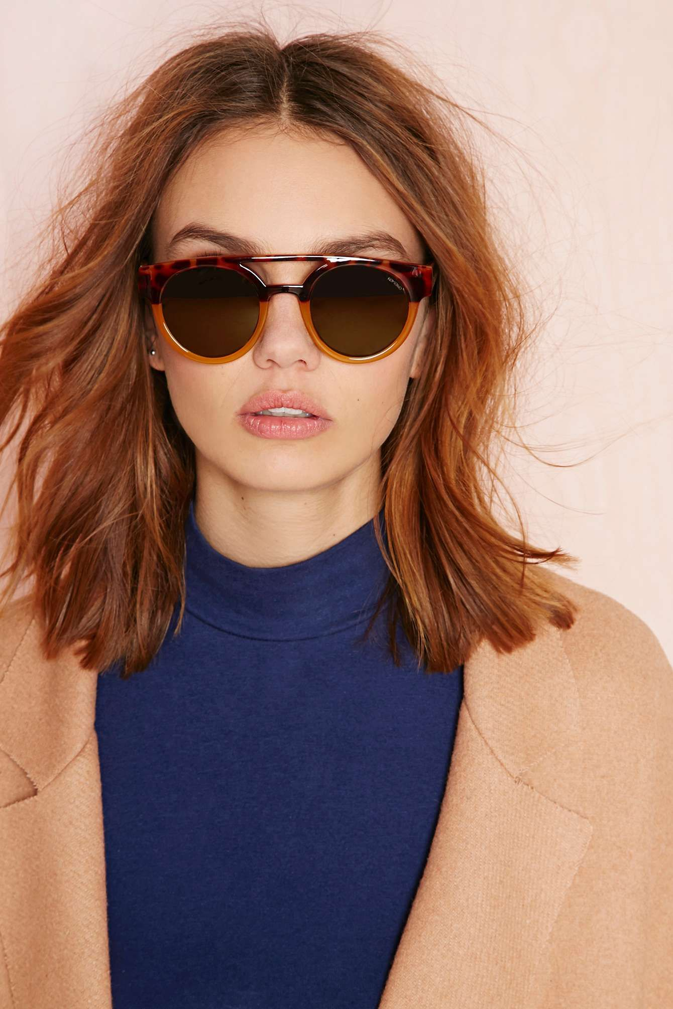 Round shades, navy and camel coat