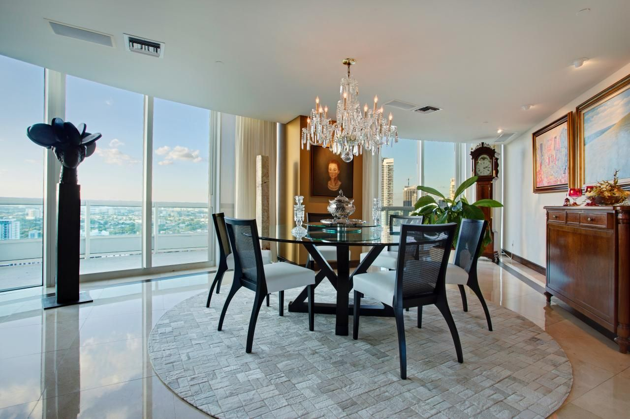 A simple round rug and crystal chandelier denote the dining area ...