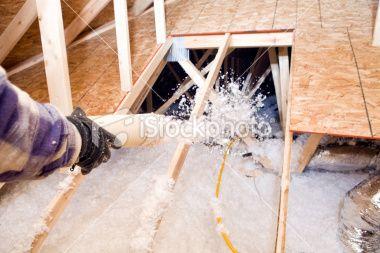 Worker Spraying Blown Fiberglass Insulation Between Attic Trusses Attic Flooring Attic Insulation Attic Remodel