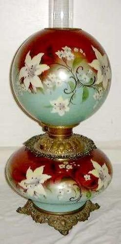 A Gone With the Wind type Victorian parlor lamp having its original green and red font and globe with hand-painted lily ddecoration. Circa 1860-1880