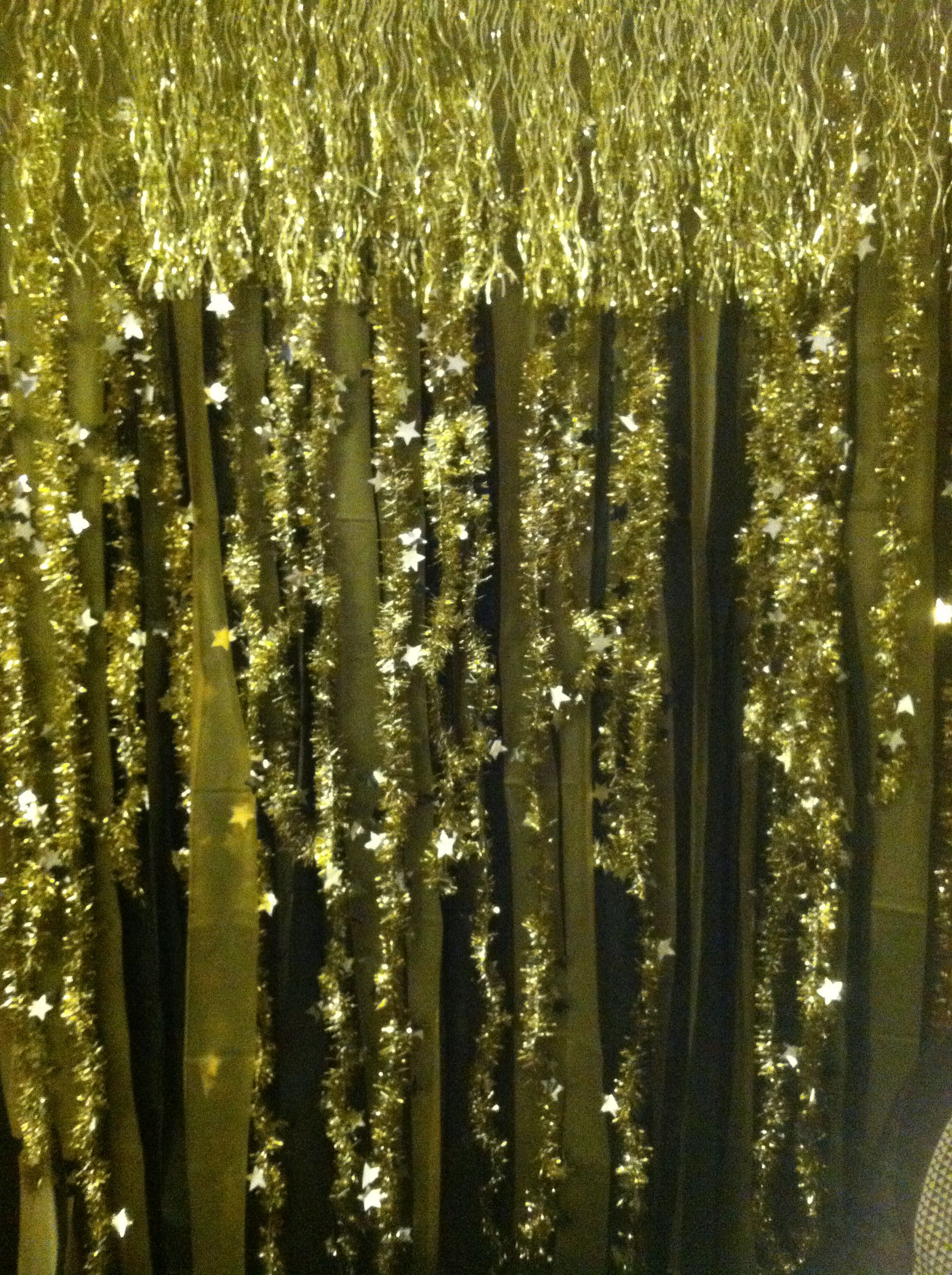 DIY New Years Eve photo booth backdrop using Dollar Tree black and gold plastic tablecloths, garland, and tinsel drape that was 50% off after Xmas.  Cut the tablecloth in wide strips then glue garland and tinsel drape. photo booth. new years eve party.