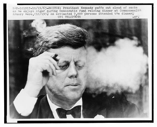 1963. 19 Octobre. President John F. Kennedy smokes a cigar during a Democratic fundraising dinner at the Commonwealth Armory at Boston University.  Photo: Bettmann/CORBIS. N° de la photo: BE043827
