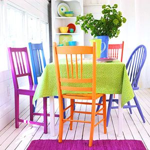 Delightful colorful kitchen chairs and decor in a simple white room. Love this.