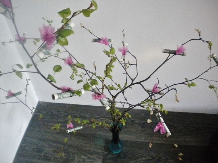 Zweige in einer Vase mit kleinen Geldrollen dekoriert