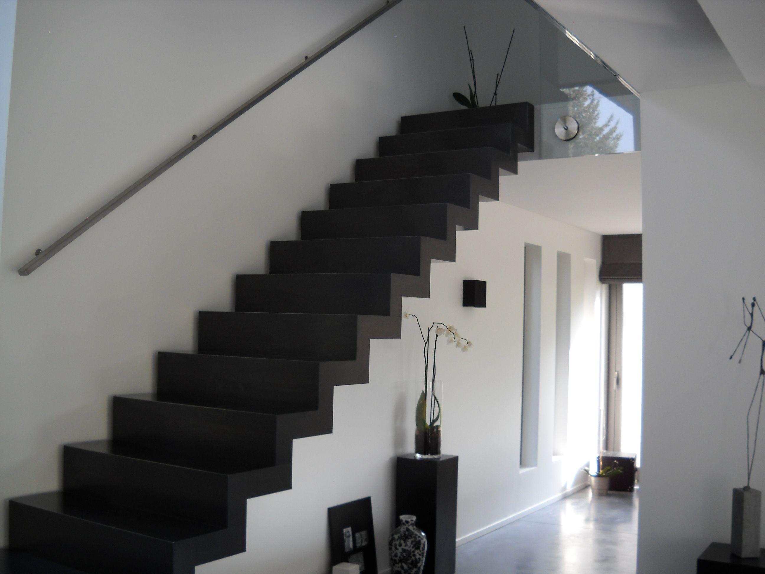 Zwarte design trap staal met strakke leuning langs de muur