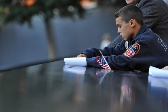 A young boy scratches the name on paper as friends and relatives of the victims of the Sept. 11 terrorist attacks on the World Trade Center attend a ceremony marking the 11th anniversary of the attacks at the National September 11 Memorial at the World Trade Center site in New York, Tuesday, Sept. 11, 2012.