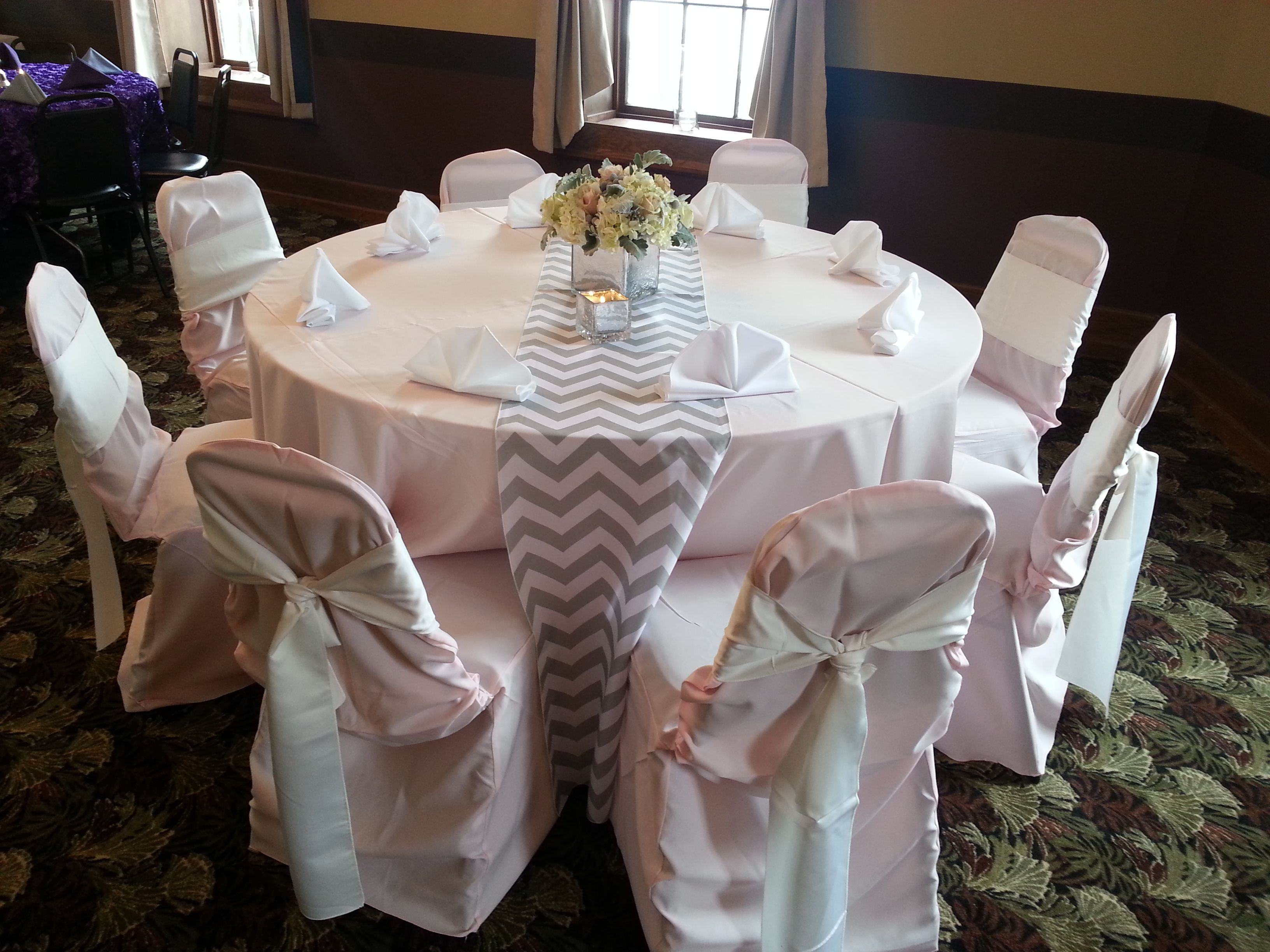 Light pink table cloth with a chevron table runner white napkins