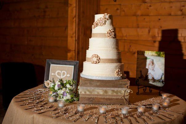 Rustic wedding cake table- I like the frames and candles on the cake ...