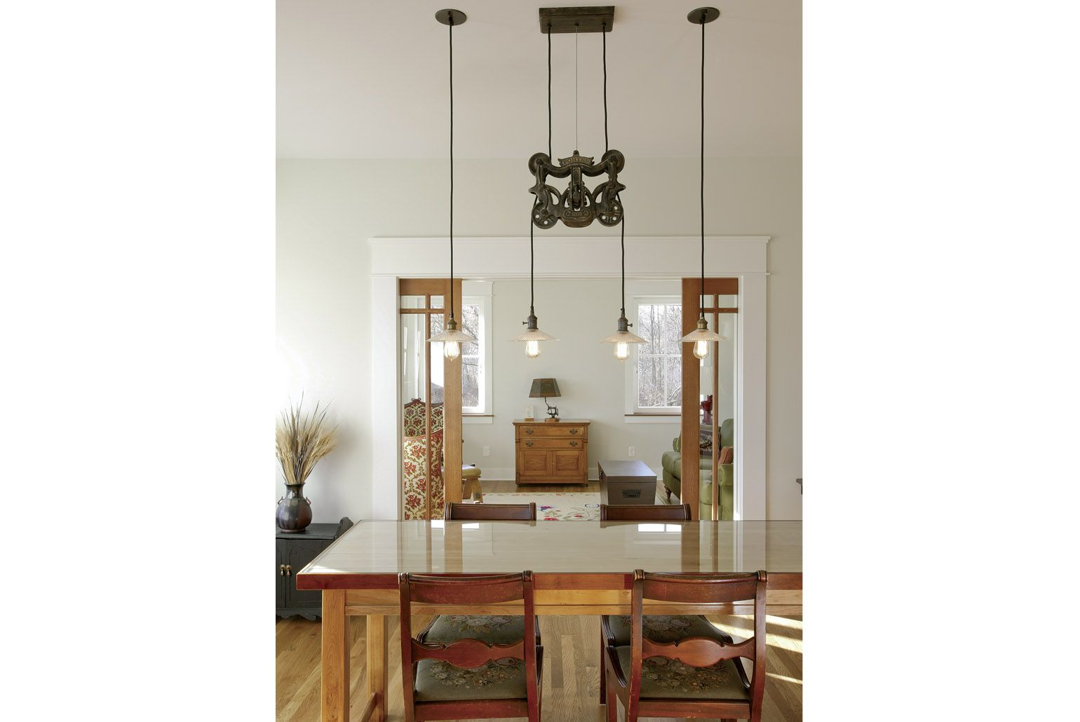 A dining room light by Restoration Hardware anchors the simple ...