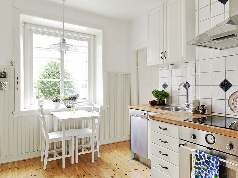 Cocina blanca con paneles de madera a media altura en la for Cocinas alicatadas