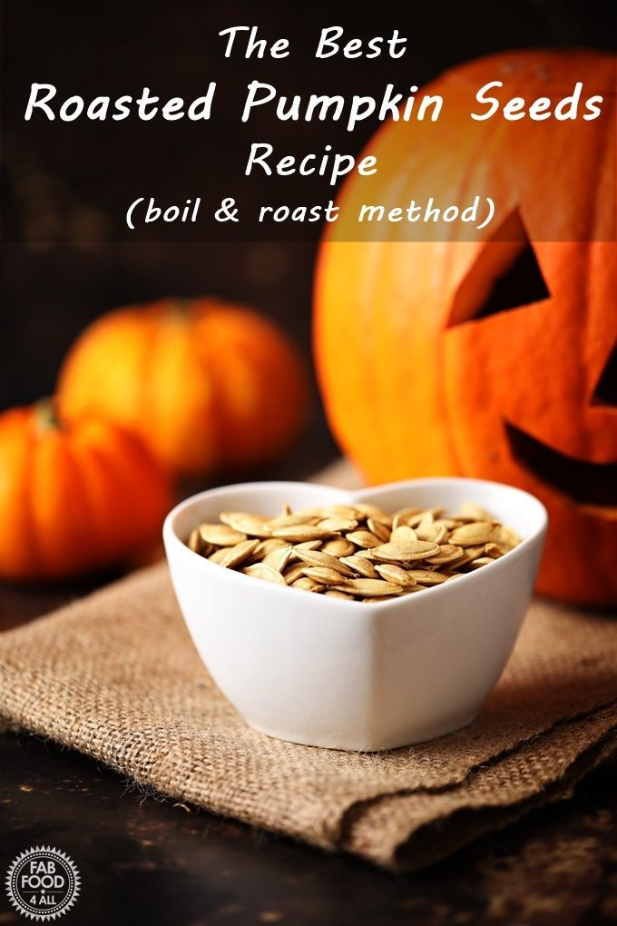 The Best Roasted Pumpkin Seeds Recipe (boil & roast) | Fab Food 4 All #roastedpumpkinseedsrecipe Roasted Pumpkin Seeds in a dish with Pumpkins & jack-o-lantern in the background. Pinterest image. #roastedpumpkinseedsrecipe