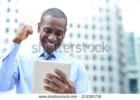 Successful businessman clenching fists with digital tablet