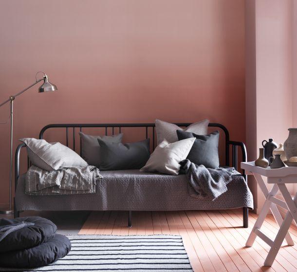 Un diván en metal negro mostrado como sofá lleno de cojines grises ...