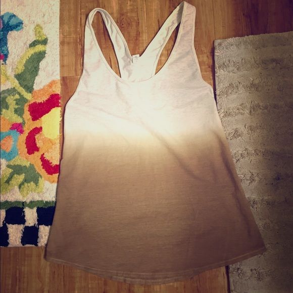Lululemon Tank Top I am selling this off white and brown Lululemon tank top. It is racerback style and is tight at the top and flares at the bottom. The white and the top is more of an off white/heather gray. It is a size 2. Worn once. No stains and is in great shape. lululemon athletica Tops Tank Tops