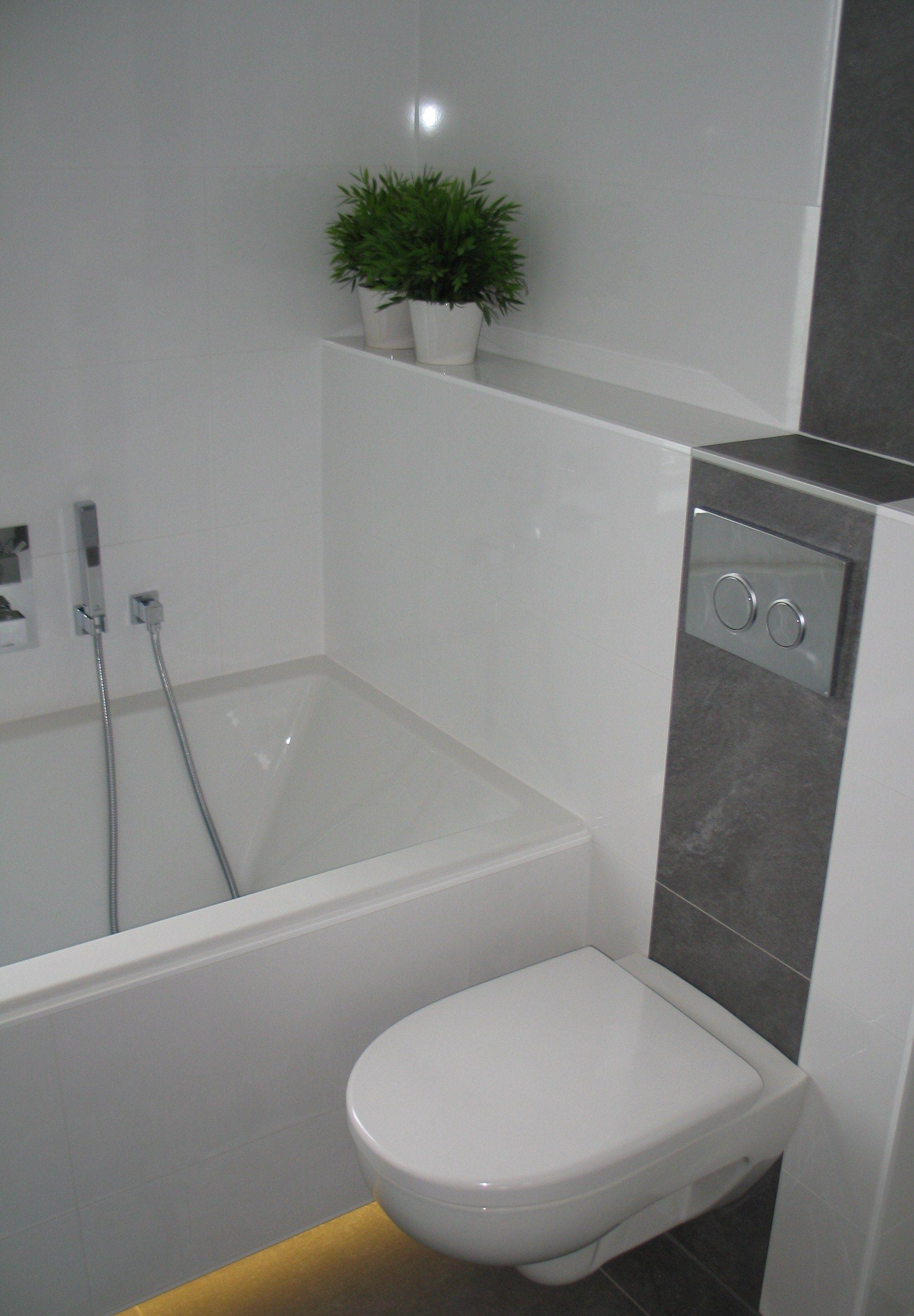 witte badkamer met bruine banen in de tegelwanden en verlichting onder het bad de bruine banen zijn van dezelfde tegels als op de vloer