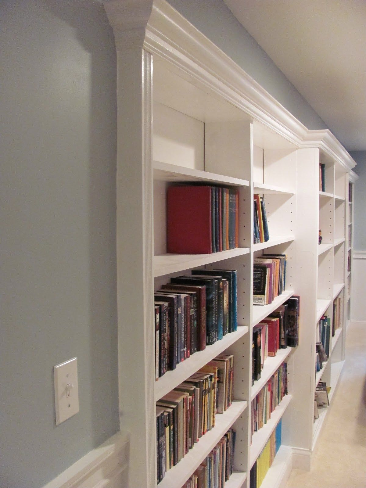 Basement Rec Room With Recessed Built In Bookshelf Under A Soffit