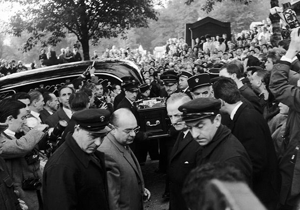 The Parisian idol died on October 11th, 1963. Edith Piaf's coffin is carried through Pere Lachaise cemetery. Her songs of love and loss in a voice that Jean Cocteau described as 'like black velvet' made Edith Piaf a Parisian idol. She was only 47 when she died  of cancer.  The Archbishop denied requests for a funeral Mass, citing Piaf's irreligious lifestyle. Thousands lined the streets to watch her funeral procession to the Père Lachaise cemetery, where more than 40,000 saw her interred.