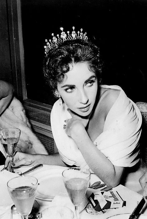 Elizabeth Taylor. The more photos I look at Liz, the more I like her, she's sort of always over it. Nice tiara and smokes combination.