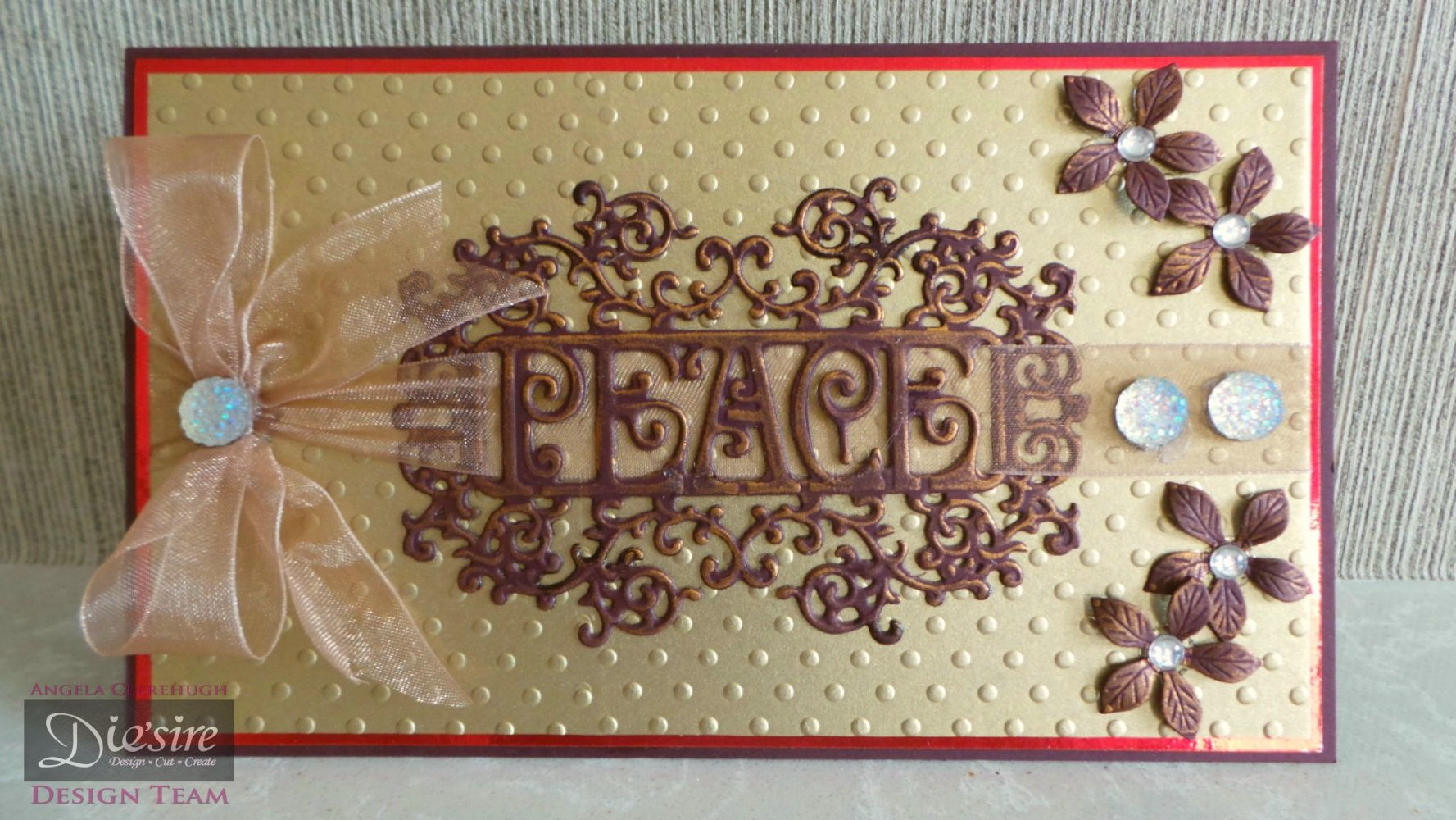 Angela Clerehugh – 7 x 5 Card – Die'sire Christmas Only Words Prestige (Peace) – Die'sire Poinsettia - Pebeo Gilding Wax (Renaissance Gold) – Collall All Purpose Glue - Burgundy Card – Red Mirror Card – Gold Card - Gems – Ribbon – Embossing Folder (Dots) - #crafterscompanion #Christmas