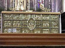 """Duomo di Monza Paliotto dell'altare maggiore (XIV secolo).Il paliotto (dal latino pallium, """"velo"""") è un pannello decorativo che viene usato in alcune chiese come rivestimento della parte anteriore di un altare. Esso può essere di stoffa, d'avorio, a mosaico, oppure lavorato con metalli preziosi, come, ad esempio, l'argento. Il paliotto può avere un valore artistico notevole. Il suo nome latino, talvolta usato anche in tempi moderni, è antependium."""