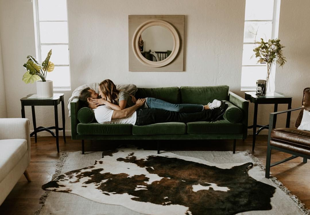 Cozy In Home Session Posing Couples Velvet Green Couch And Boho Faux Cow Hide Rug Ph Hide Rug Living Room Cowhide Rug Living Room Boho Chic Living Room Decor