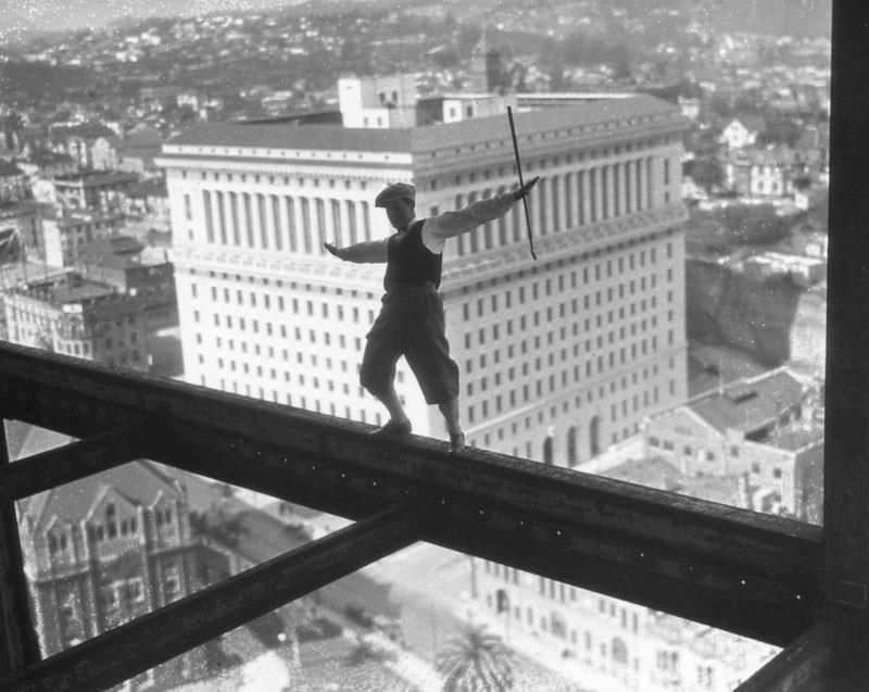 A stunt man, wearing golfing attire and holding a golf club, is photographed on a girder of the present L.A. City Hall while under construction in 1927.