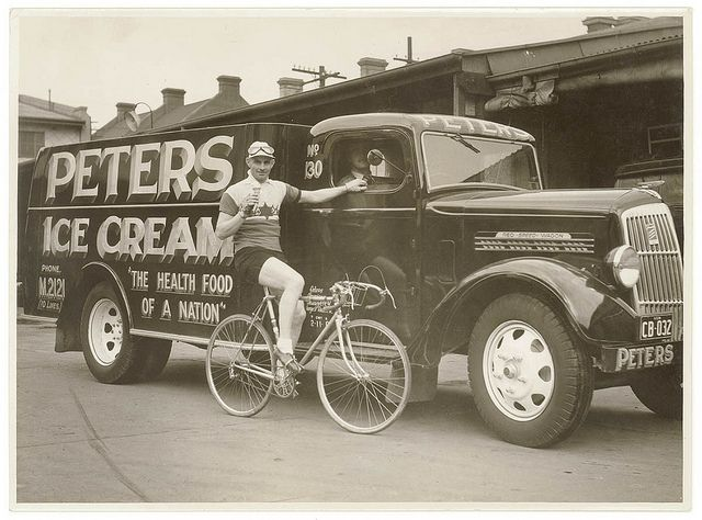 Hubert Opperman eating an ice cream next to a Peter's Ice Cream Reo truck,1936, by Sam Hood