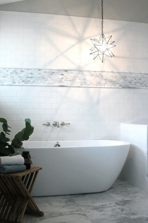 Beautiful bathroom with sloped ceiling over subway tiles accented with a mini marble brick tile border illuminated by an off center Moravian Star Pendant.