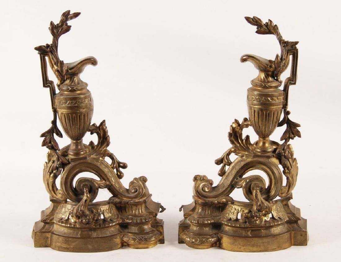 "Lot: PAIR OF FRENCH 19"" HIGH GILT BRONZE CHENETS, Having a  Classical Style Ewer, surrounded by foliated vine resting on a ""C"" scroll formed stand. France 19th century"