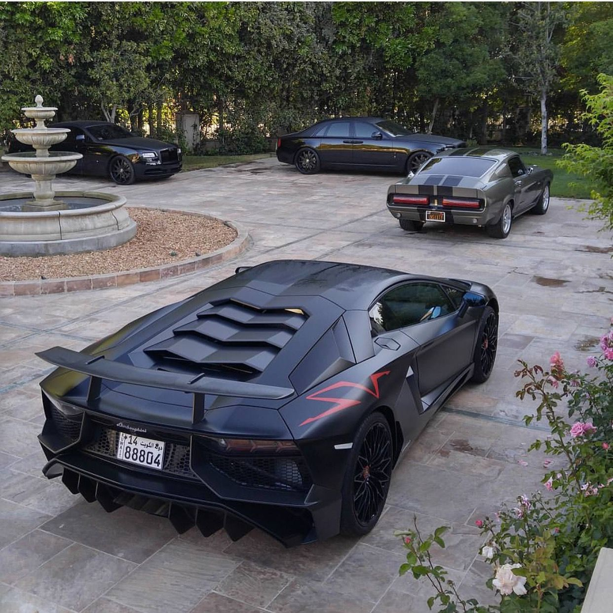 """2 Rolls Royce Ghosts painted in Gloss Black, 1969 Ford Mustang GT500 painted in Silver and a Lamborghini Aventador Super Veloce Coupe painted in Nero Nemesis w/ Red """"SV"""" stickers Photo taken by: @thedaekestride on Instagram (He is also the owner of the cars)"""