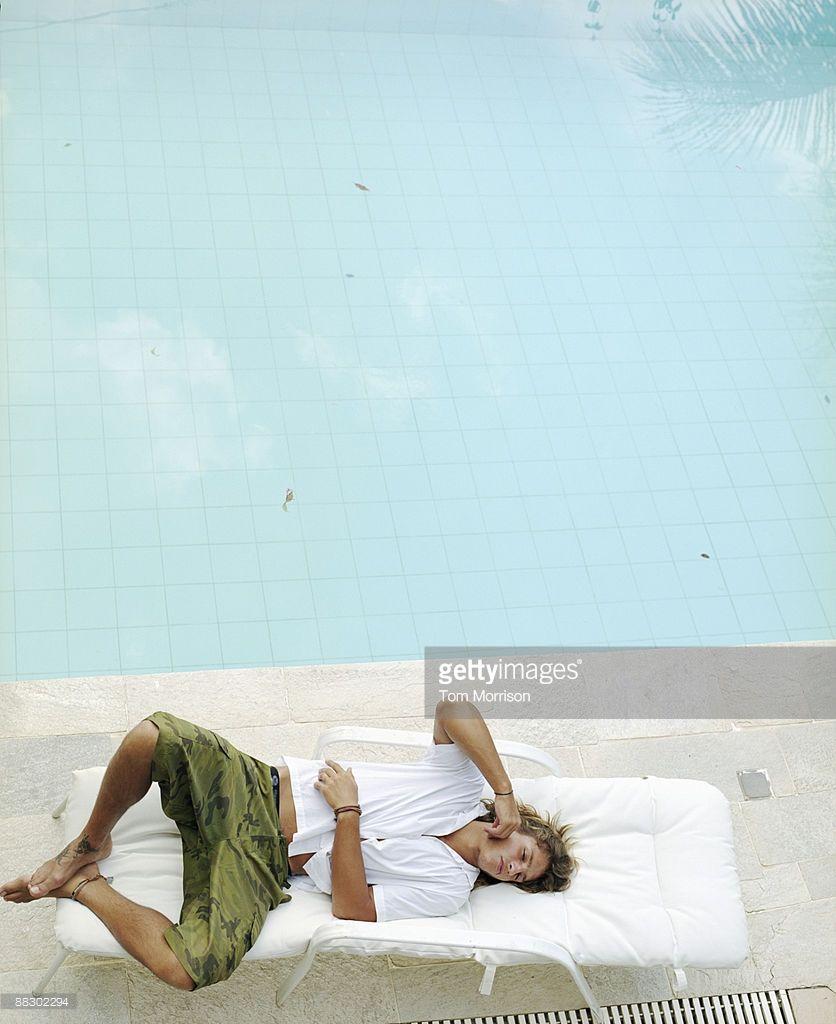 Man Lying Down On Lounge Chair At Beach Beach Photo Image