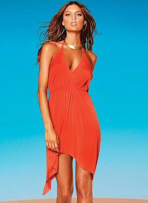 Slinky cayenne halter dress with adjustable tie at waist and asymmetrical hemline by Vitamin A Swimwear, $130.00