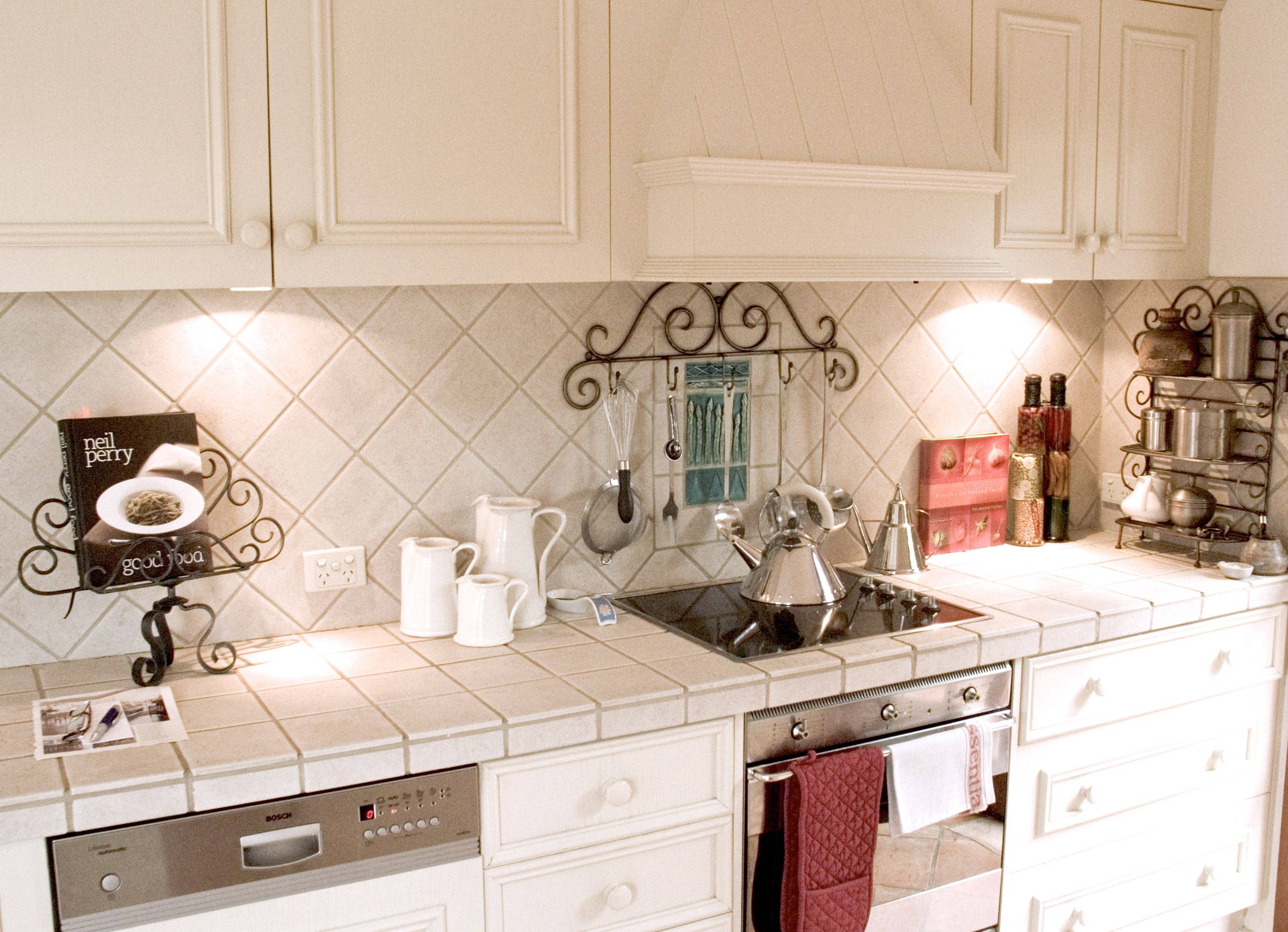 french provincial white kitchen with tiled bench and matching wall
