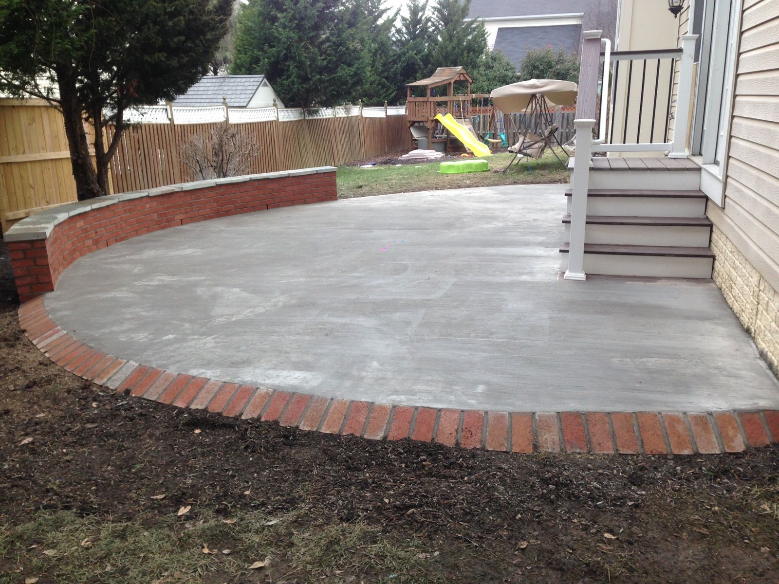 Concrete Patio With A Brick Seating Wall And Border In Ashburn