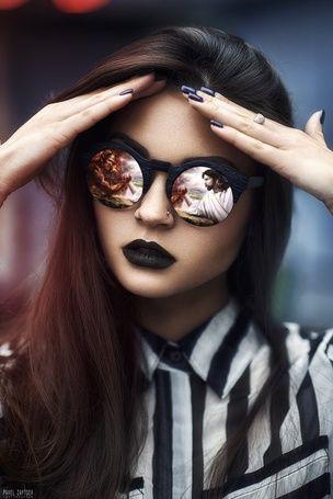 Девушка в очках держит руки у лба, а ее очках отражается ...