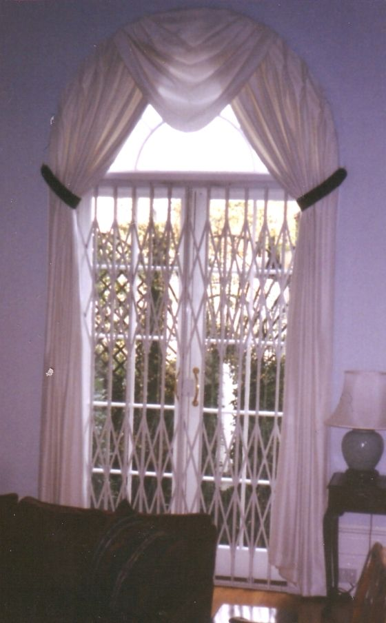 Arched window dressed with voile curtains & swag