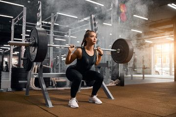 Beautiful young powerlifter squatting in modern fitness studio using heavy barbell, looking aside ex...