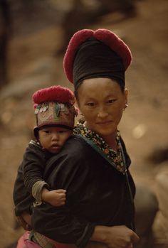 Laos | Portrait of a Hmong woman carrying her child wearing a traditional headdress | © W.E. Garrett