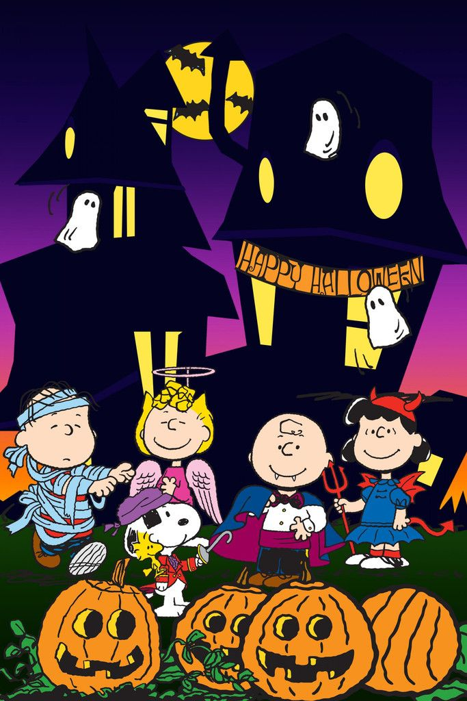 peanuts characters dressed in costume in front of a haunted house