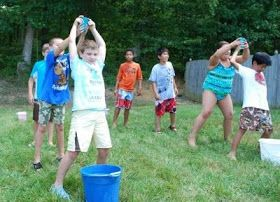 Water relay - pour a cup of water behind you, next person catches and pours behind them, first team to reach a fill line in their bucket wins.  End of the year game!