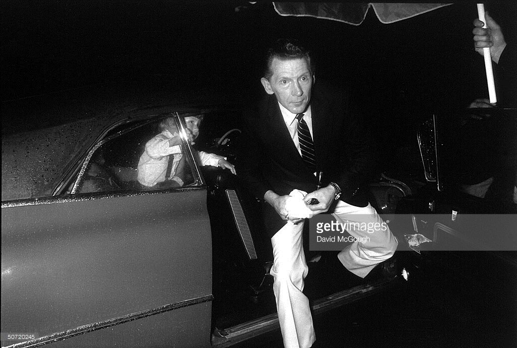 Singer Jerry Lee Lewis getting out of car (w. son, Jerry Lee Lewis III, still in backseat) arriving at party for film Great Balls of Fire, based on his life story.