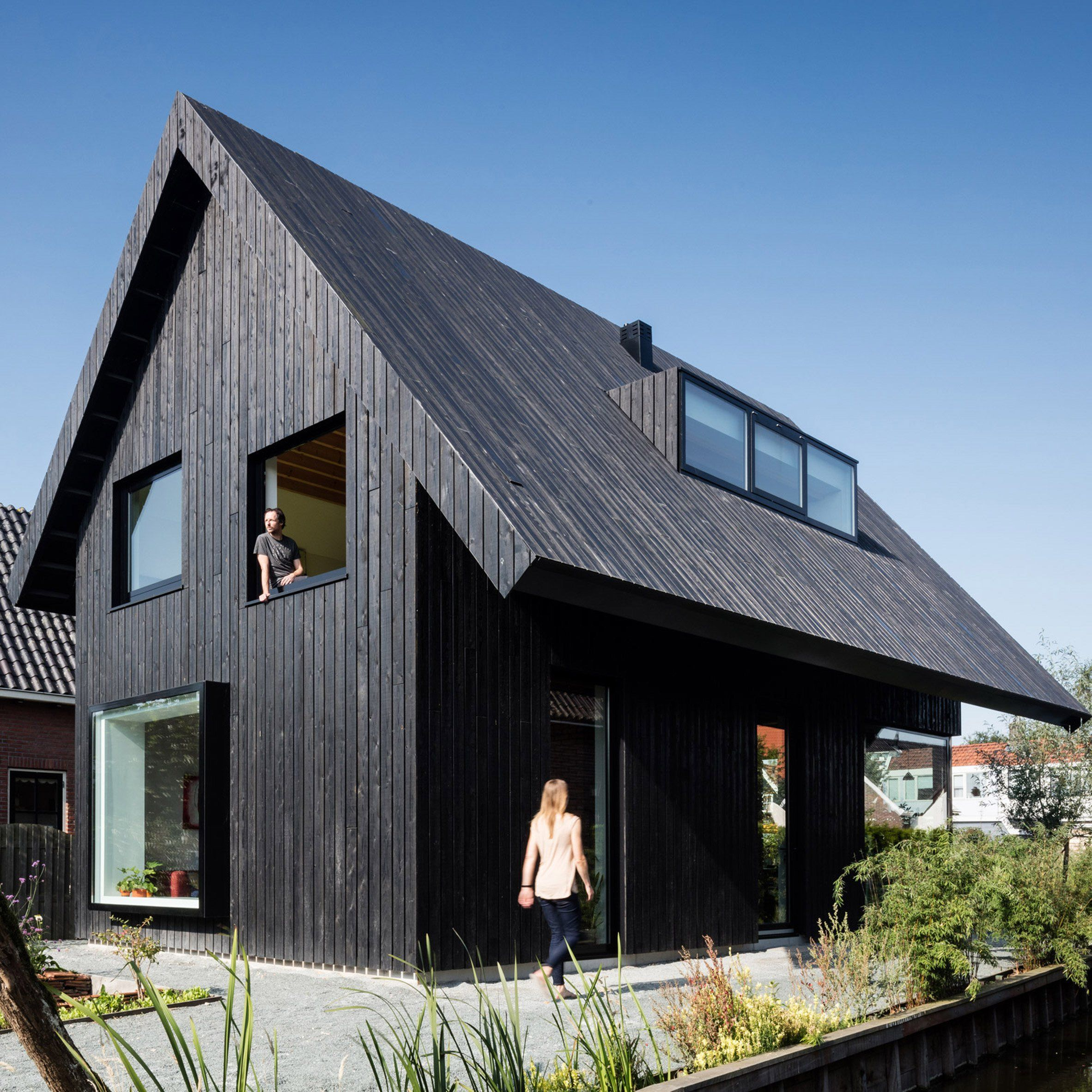 This Modern House With A Gable Roof And Round Windows On The