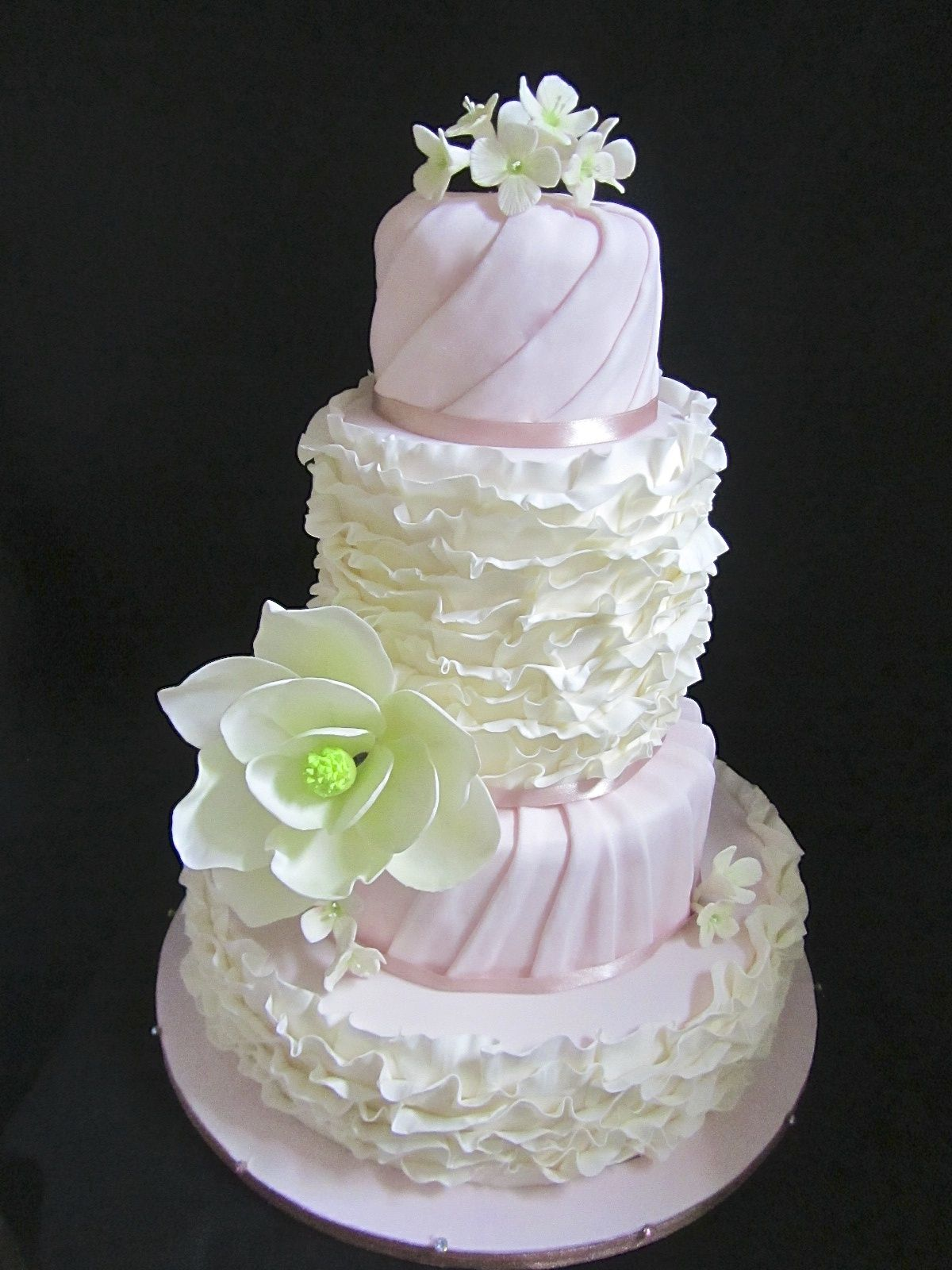 Pink and Ivory. Sweet and dreamy wedding cake with ruffles and fondant magnolia.