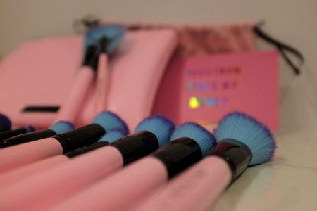 face and eye makeup brushes that have pink handles with