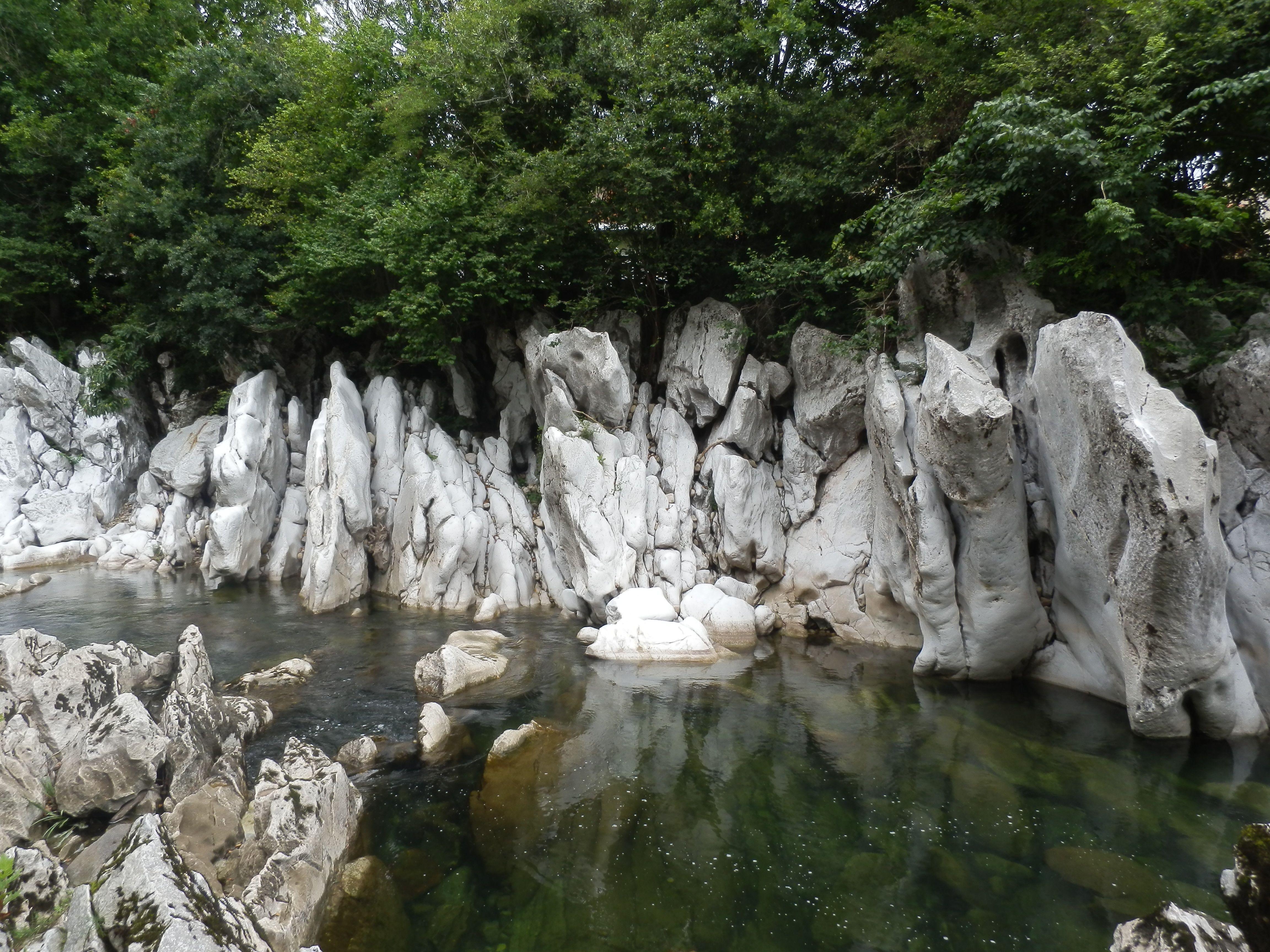 Una enorme pared de roca blanca desgastada por el paso del agua del río
