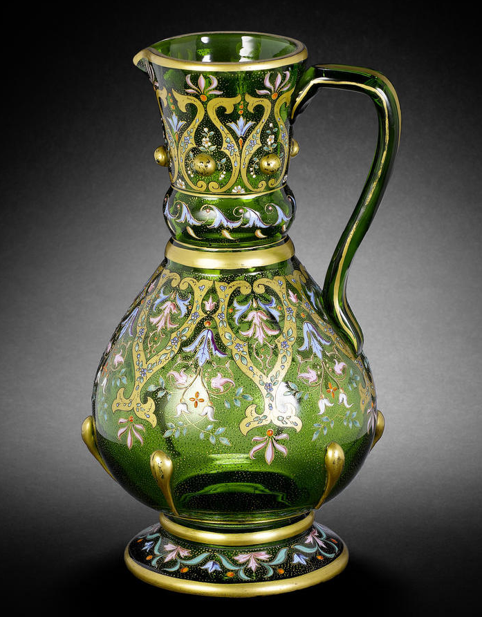 An enamelled glass Ewer  Bohemia, circa 1880 of pear-shaped form on a flared foot with strap handle and flaring neck with pouring spout, decorated in gilt and polychrome enamel, the body and neck with bands of palmette motifs containing and interspersed by flowerheads and foliate motifs